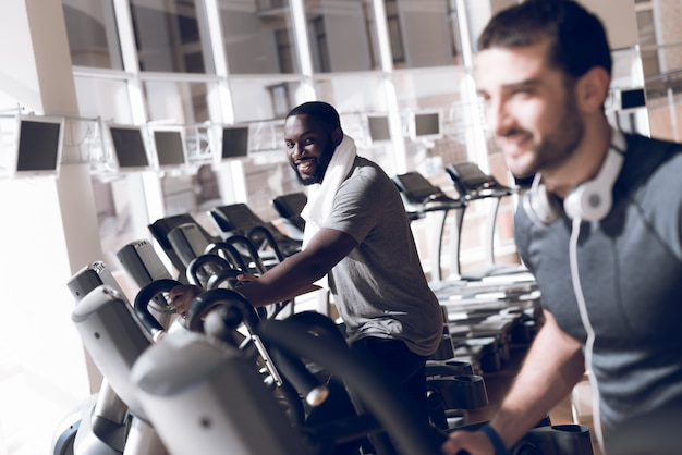 Twee mannen zijn bezig met de loopbanden in de moderne sportschool Premium Foto