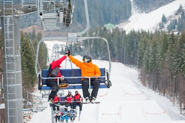 Twee mannetje berijdt de skistoel lift samen de berg op Premium Foto