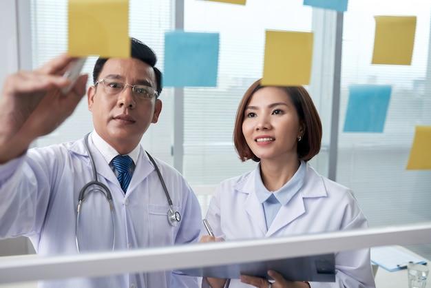 Twee medische collega's beoordelen de geheugenstickers op het glasbord Gratis Foto