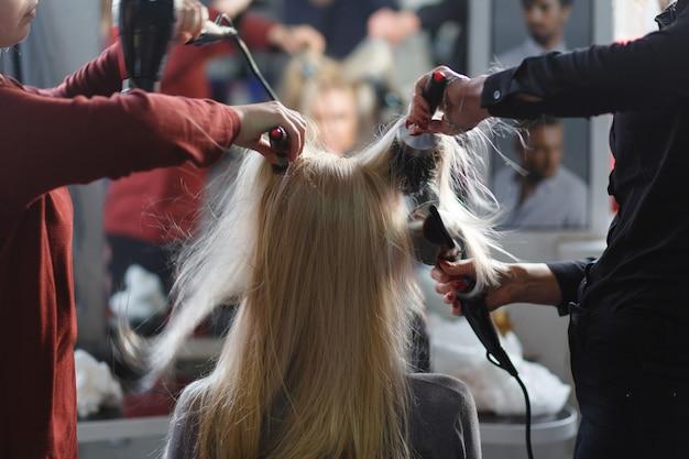 Twee meesters tegelijkertijd gedroogd met haardrogers haar blonde model in schoonheidssalon. achteraanzicht. Premium Foto