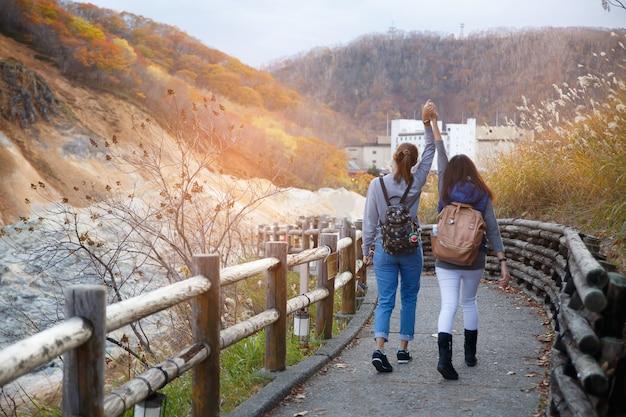Twee meisjes die op de straat en de rode gele esdoornboom lopen in de herfstseizoen, dat uit japan wordt genomen. Premium Foto