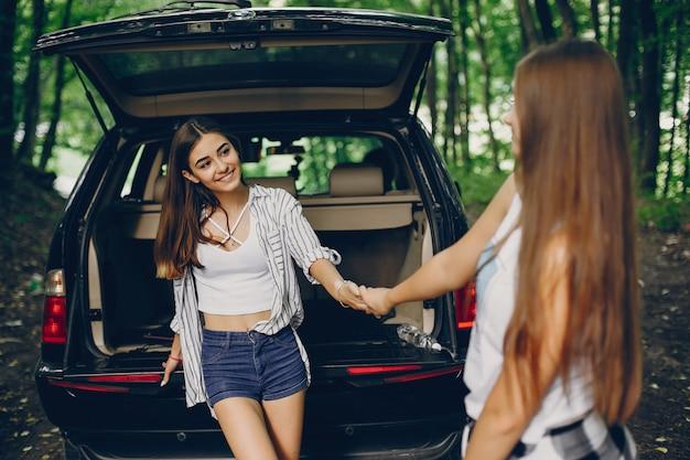 Twee meisjes in de buurt van de auto Gratis Foto
