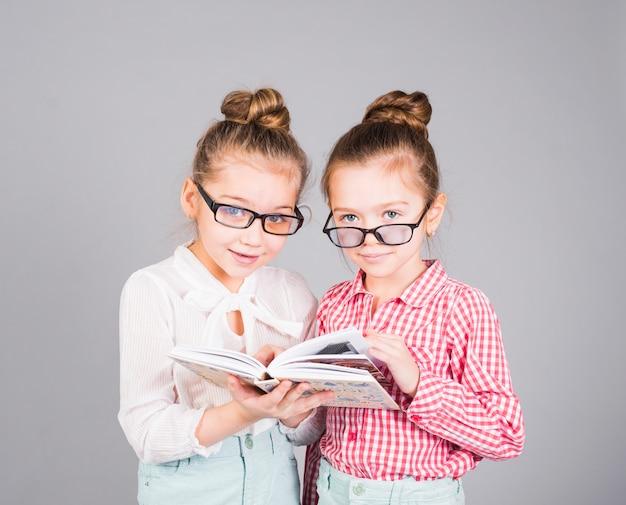 Twee meisjes in glazen die zich met boek bevinden Gratis Foto