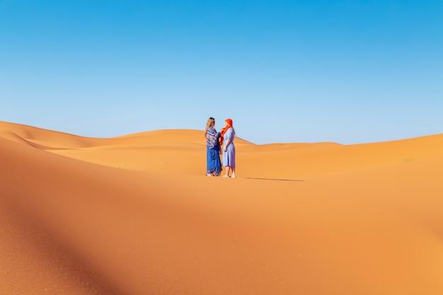 Twee meisjes in hoofddoek in de sahara woestijn. Premium Foto