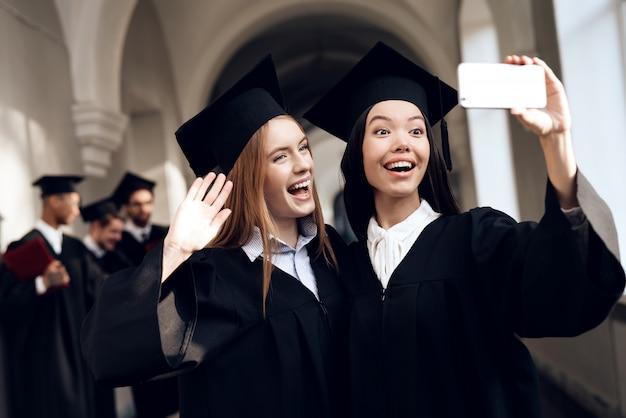 Twee meisjes in zwarte mantels maken selfie. Premium Foto