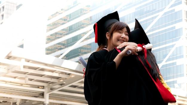 Twee meisjes in zwarte toga's en houden diploma-certificaat zitten en lachend met gelukkig afgestudeerd. Premium Foto