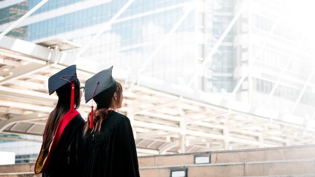 Twee meisjes in zwarte toga status kijken omhoog aan de hemel met gelukkige gediplomeerden. Premium Foto