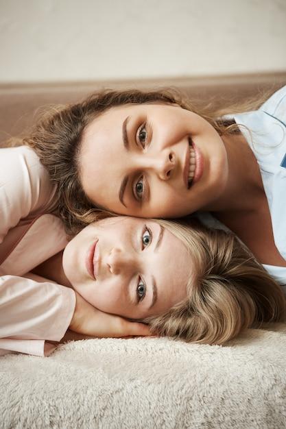 Twee meisjes met een hechte relatie, die zich zusjes voelen. verticaal schot van knappe op bank liggen en vrouwen die breed glimlachen. charmante krullende vriend die op het hoofd van haar bestie ligt Gratis Foto