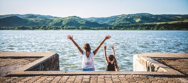 Twee meisjes met opgeheven handen die zich door de rivier bevinden Premium Foto