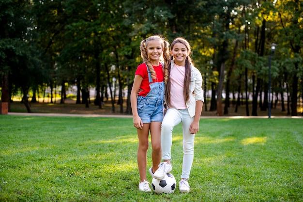 Twee meisjes met voetbalbal openlucht Gratis Foto