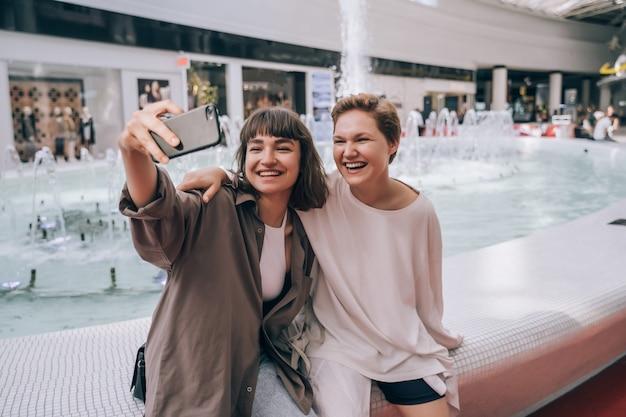 Twee meisjes nemen een selfie in het winkelcentrum, een fontein Gratis Foto