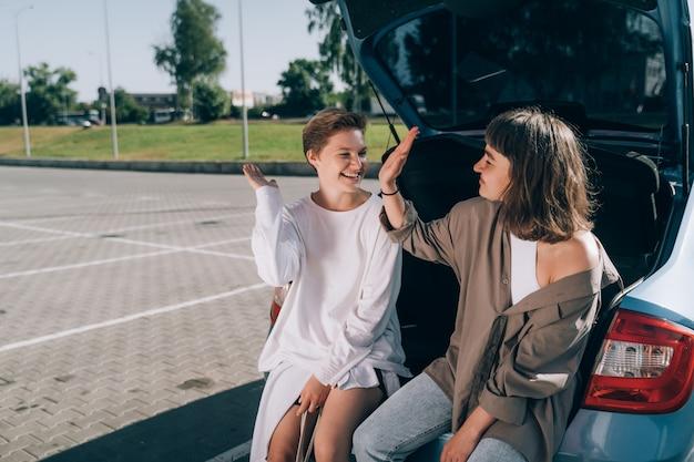 Twee meisjes op de parkeerplaats bij de open kofferbak poseren voor de camera. Gratis Foto