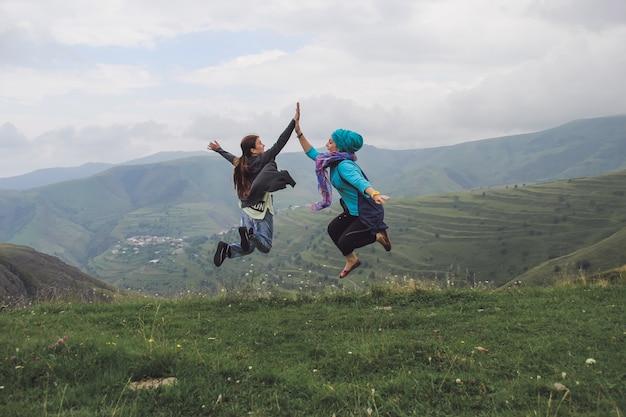 Twee meisjes springen in de lucht en klappen in hun handen in de bergen Premium Foto