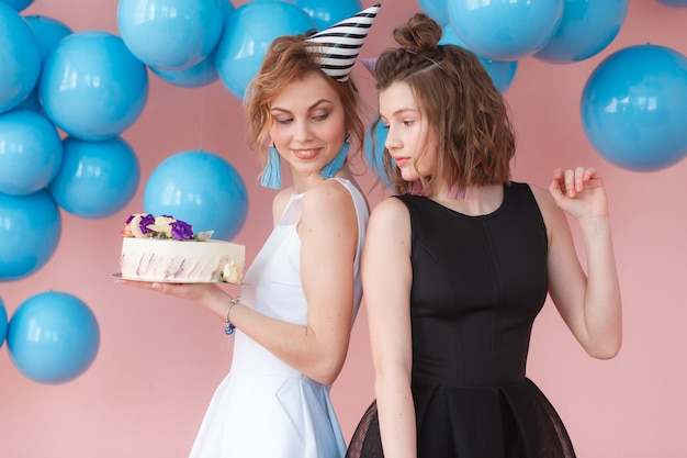 Twee meisjes van de tiener leuke manier die de gelukkige cake van de verjaardags witte room houden. Gratis Foto