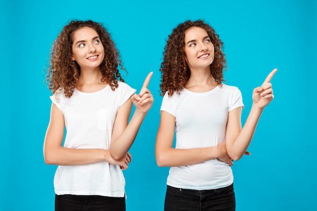 Twee meisjestweelingen glimlachen, wijzend vingers weg over blauwe muur Gratis Foto