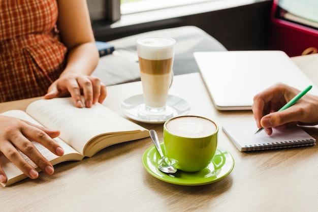 Twee mensen die in koffie met kop van koffie en latte bestuderen Gratis Foto