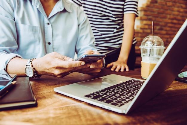 Twee mensen die mobiel gebruiken tijdens een vergadering in de coffeeshop voor de baan van het mkb Premium Foto