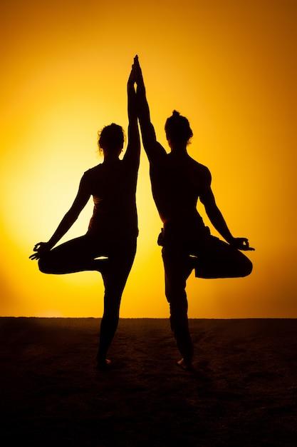 Twee mensen die yoga in het zonsonderganglicht uitoefenen Gratis Foto