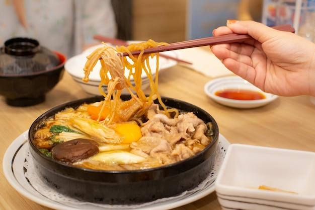 Twee mensen eten varkensvlees shabu of hete pot. familie tijd. Premium Foto