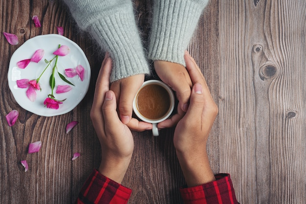 Twee mensen houden van kopje koffie in handen met liefde en warmte op houten tafel Gratis Foto
