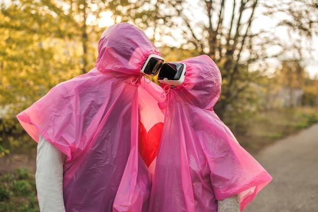 Twee mensen kijken elkaar romantisch aan in roze plastic regenjassen en vr-headset Gratis Foto
