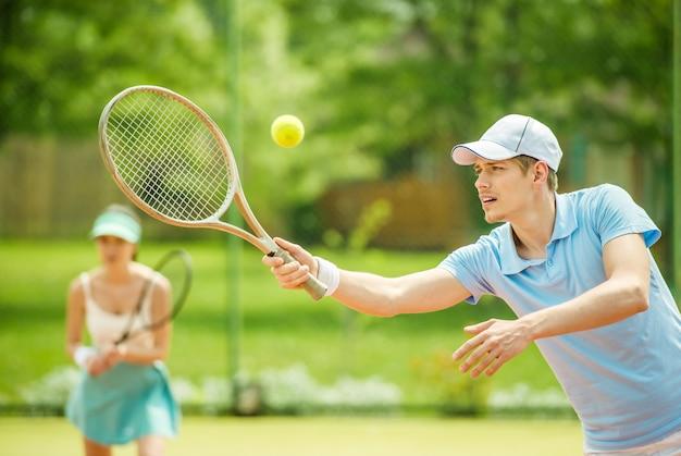 Twee mensen spelen dubbel op de tennisbaan. Premium Foto