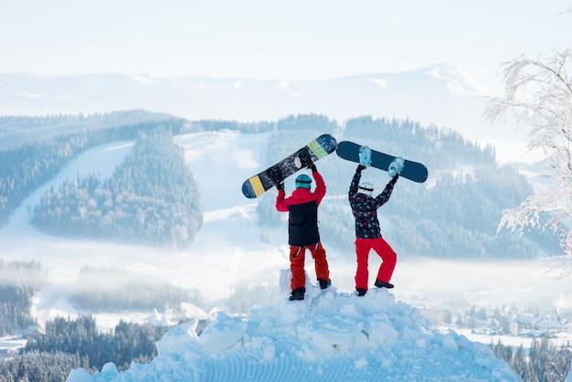 Twee mensen staan met hun rug op een sneeuwbank en heffen hun snowboards op tegen een witte waas van met sneeuw bedekte bergen en bossen in het winterskigebied. Premium Foto