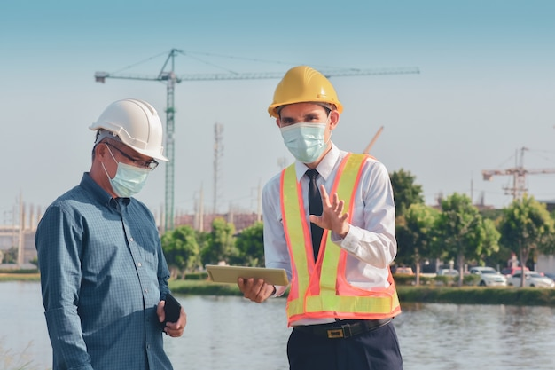 Twee mensen werken aan de bouw van de site en praten dan over een bouwproject Premium Foto