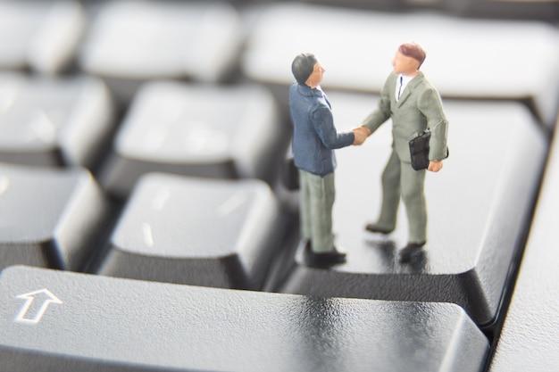 Twee miniatuurzakenlieden die handen schudden terwijl status op de toetsen van een zwart toetsenbord. Premium Foto