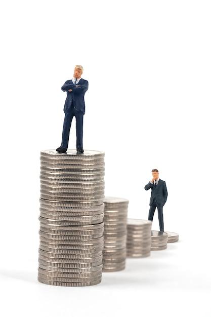 Twee miniatuurzakenlieden die zich op muntstukstapels bevinden Premium Foto