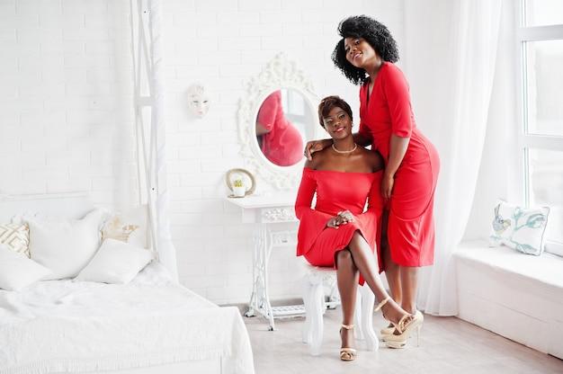 Twee mode afrikaanse amerikaanse modellen in rode schoonheidskleding, sexy vrouw die avondtoga stellen bij witte uitstekende ruimte. Premium Foto