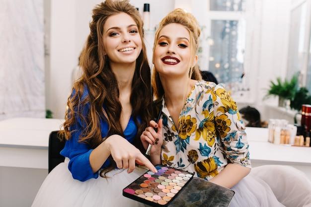 Twee modieuze aantrekkelijke modellen met stijlvolle make-up, luxe kapsel met plezier samen in kapper salon Gratis Foto
