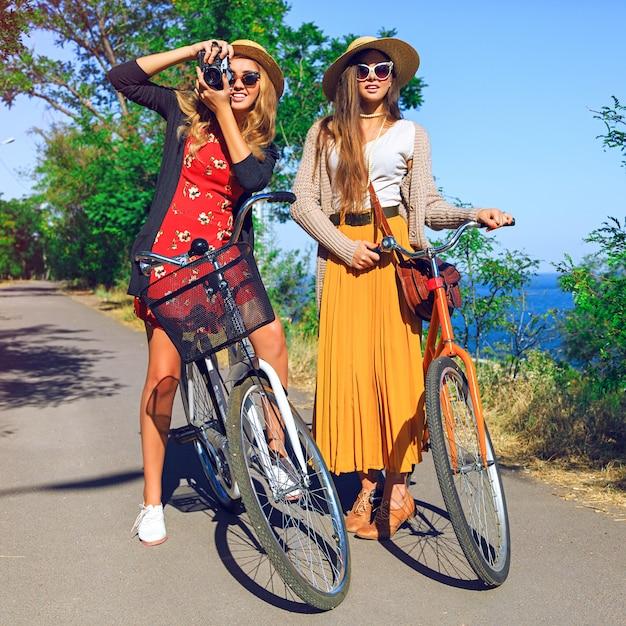 Twee mooie beste vriendenmeisjes worden gek, hebben plezier en leuke positieve emoties, wandelen met retrofietsen, zeg hallo. stijlvolle vintage outfits dragen, retro camera vasthouden. Gratis Foto