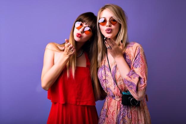 Twee mooie blonde en donkerbruine vrouwen die luchtkus naar u sturen, studio violet ruimte, vintage elegante jurken en boho-zonnebrillen. Gratis Foto