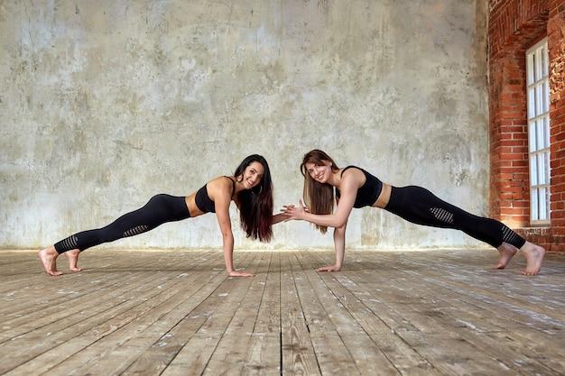 Twee mooie glimlachende, fitnessmeisjes die oefeningen in de fitnessruimte doen geven vijf. Premium Foto