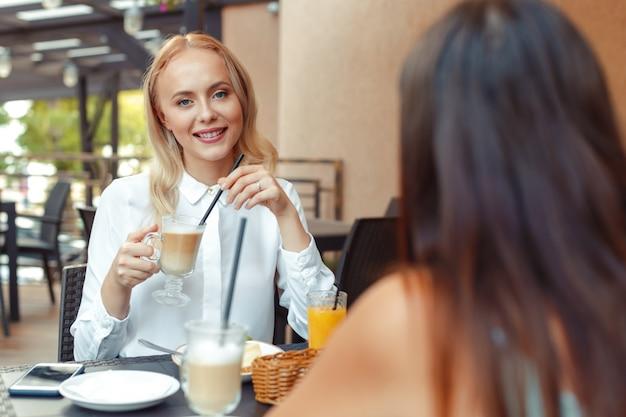 Twee mooie jonge meisjes zitten bij de tafel in café Premium Foto