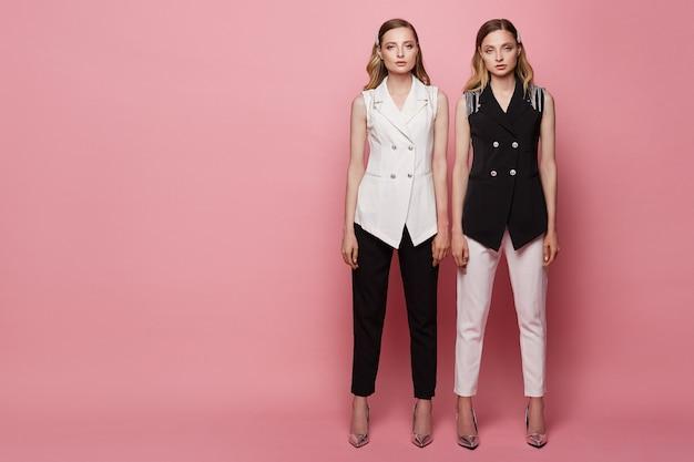 Twee mooie jonge tweeling vrouwen met slanke perfecte lichamen in zwart-wit pakken, met make-up en emotieloze gezichten, poseren op volle lengte op de roze achtergrond, geïsoleerd Premium Foto
