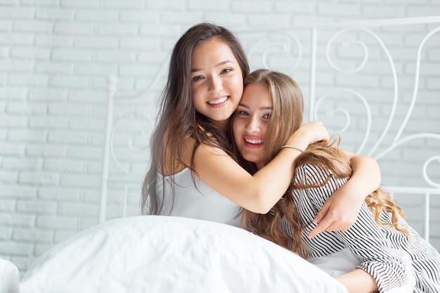 Twee mooie jonge vrouwen in bedpyjama'spartij Premium Foto