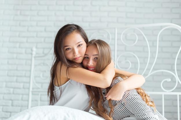 Twee mooie jonge vrouwen in de partij van bedpyjama's Premium Foto