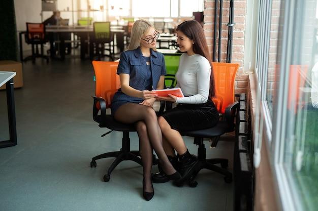 Twee mooie jonge vrouwen in het kantoor op fauteuils Premium Foto