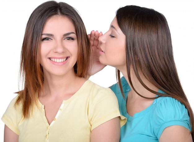 Twee mooie jonge vrouwen roddelen. Premium Foto