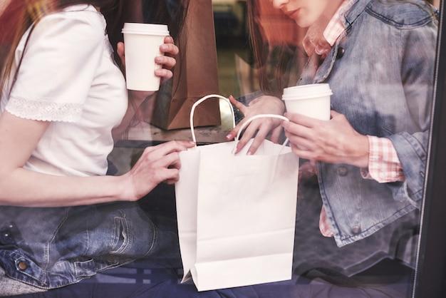 Twee mooie jonge vrouwen zitten in een café, koffie drinken en hebben een aangenaam gesprek na het winkelen. Gratis Foto