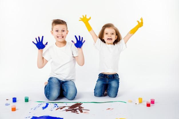 Twee mooie jongen en meisje van kindvrienden tekenen foto's met verf Premium Foto