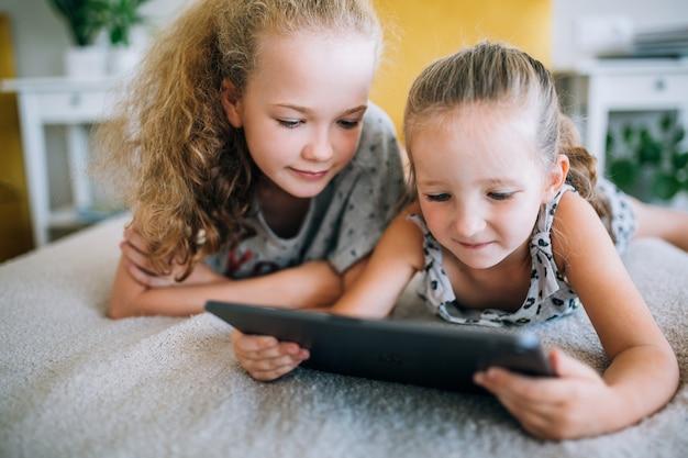 Twee mooie kleine zusjes die in bed liggen en naar het scherm van een tablet kijken, slimme kinderen die slimme technologie gebruiken Premium Foto