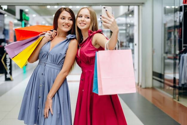 Twee mooie meisjes maken selfies in het winkelcentrum na het winkelen Premium Foto