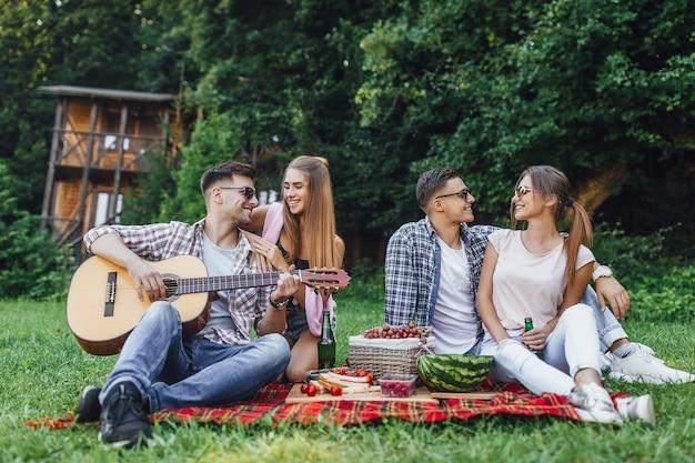 Twee mooie meisjes met twee jongens zitten in een park op een deken met gitaar, ze hebben picknick en luisteren melodie van gitaar Premium Foto