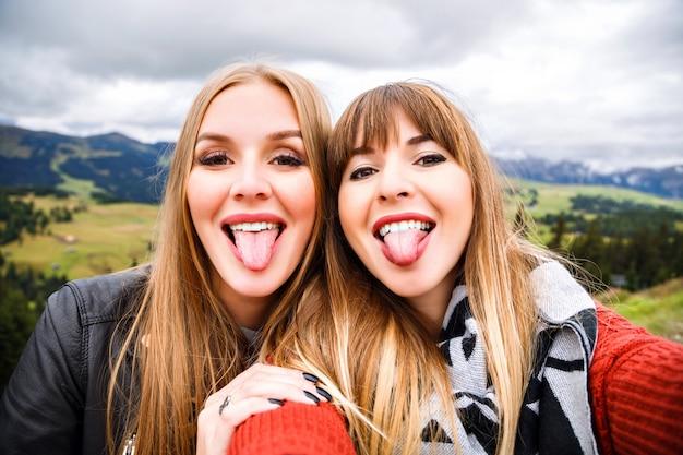 Twee mooie reizigersmeisjes die grappige selfie maken bij bergen. lange tongen laten zien, gek worden. Gratis Foto