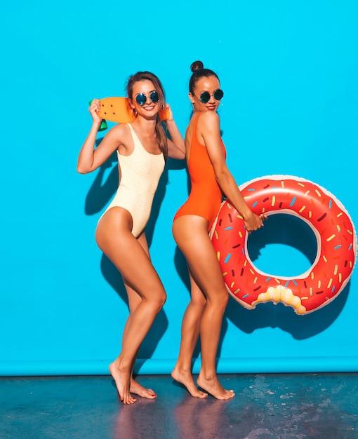 Twee mooie sexy glimlachende vrouwen in badpakken van de zomer de kleurrijke badmode. meisjes in zonnebril. positieve modellen met plezier met kleurrijke cent skateboard. met donut lilo opblaasbaar matras Gratis Foto
