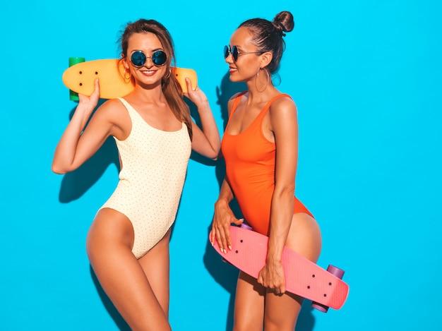 Twee mooie sexy glimlachende vrouwen in badpakken van de zomer de kleurrijke badmode. trendy meisjes in zonnebril. positieve modellen met plezier met kleurrijke penny skateboards. geïsoleerd Gratis Foto