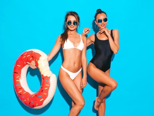 Twee mooie sexy glimlachende vrouwen in de zomer witte en zwarte badkleding badpakken. meisjes in zonnebril. positieve modellen die plezier hebben met de opblaasbare matras van donutlila. geïsoleerd op blauwe muur Gratis Foto